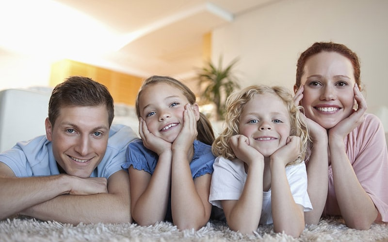 Happy family enjoying their recently maintained ac unit in their home