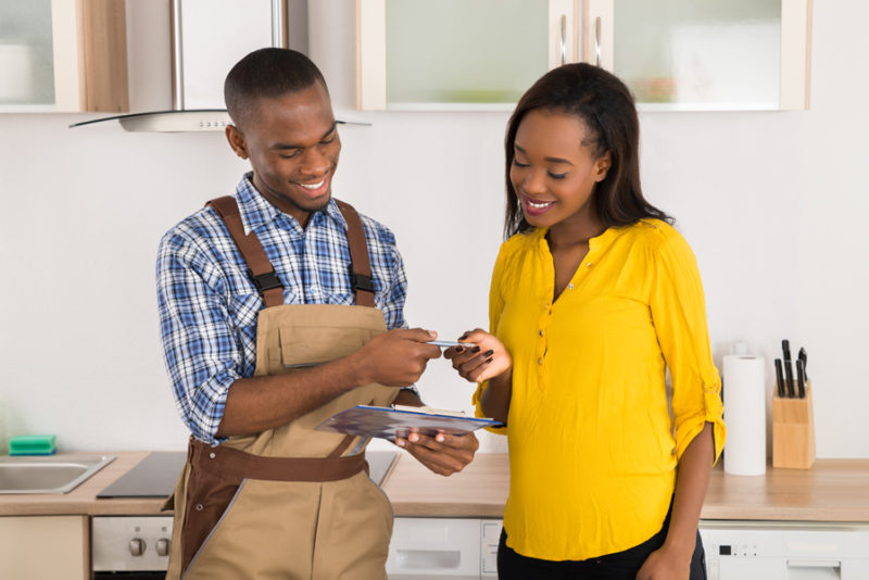 Young Happy Woman And Serviceman Standing In Kitchen With Clipboard