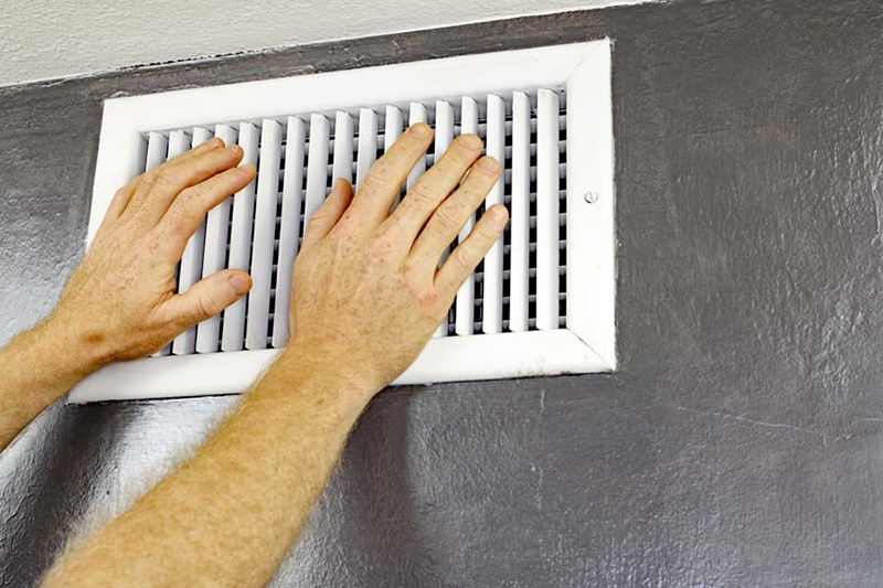 hands in front of HVAC vent air conditioner ac blowing hot air