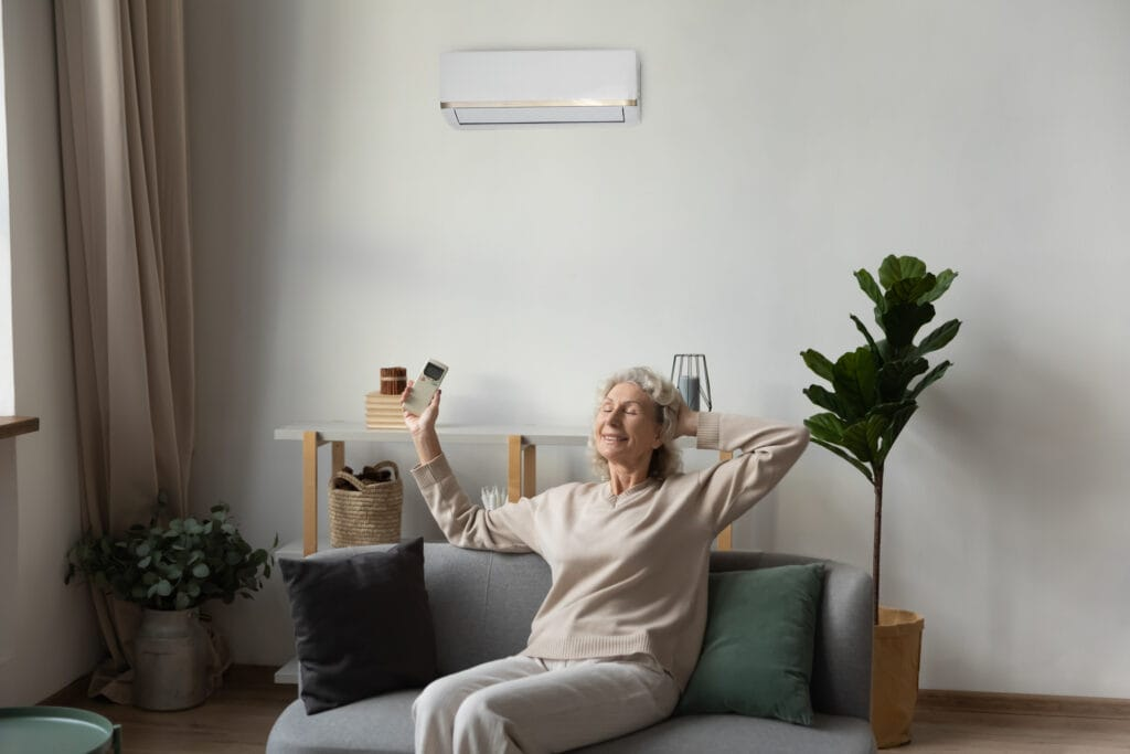 smiling elderly grandmother breathe enjoy healthy air quality under AC system at home
