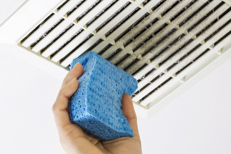 Close up horizontal photo of female hand cleaning dirty bathroom air ducts with blue sponge in Savannah GA.