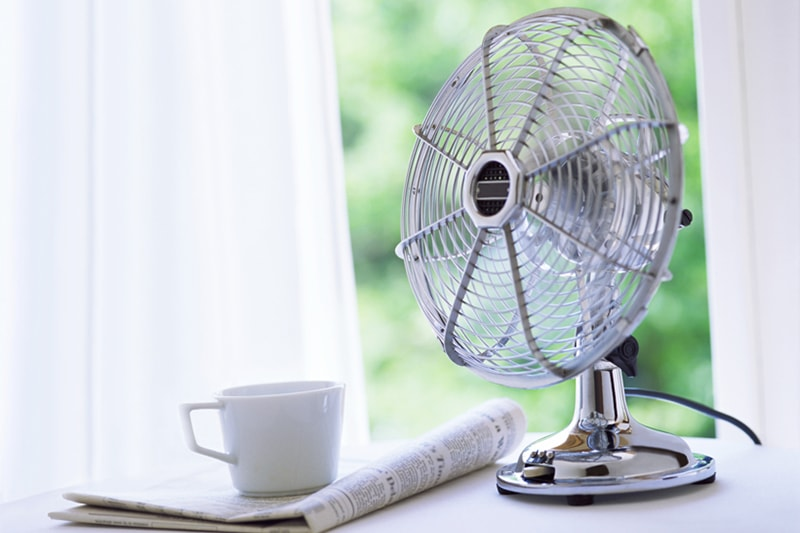 Electric fan turned on sitting on a white table with a cup of coffee, 4 HVAC Habits That Can Wreak Havoc on Your Home's Efficiency | AC