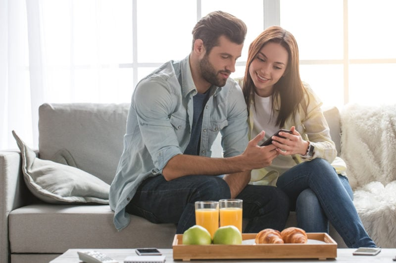 Young woman and man family couple indoors using smartphone to apply for financing