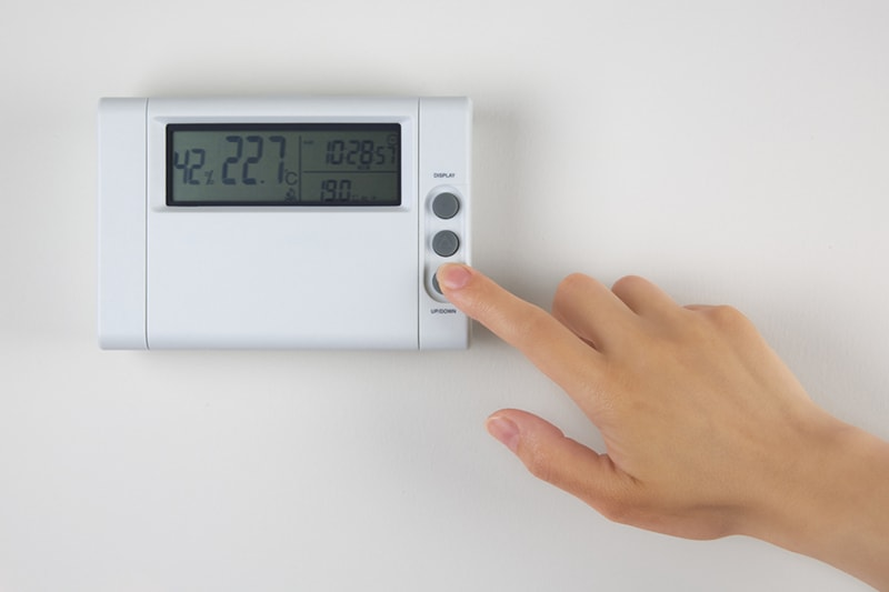 A hand controlling a thermostat, 3 HVAC Problems That Can Reduce the Comfort in Your Home