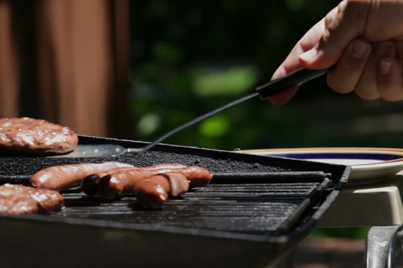 Grilling hotdogs on a grill in order to save energy in their Savannah home