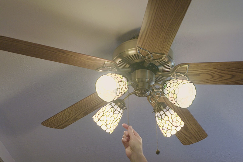 person turning on their ceiling fan to save energy and keep their home cool