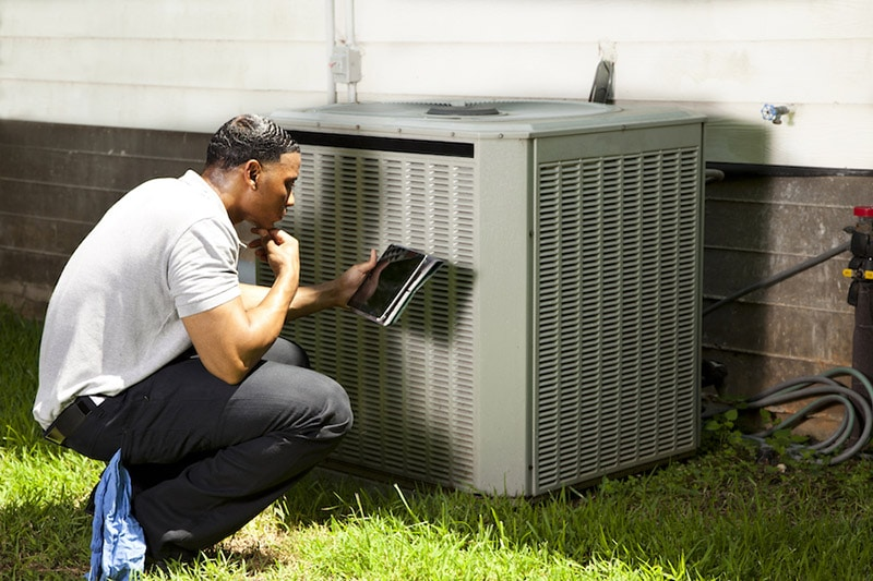 Home inspector, repairman uses digital tablet to check air conditioners, Does the HVAC System Pull In Air From Outside? | Hilton Head, SC