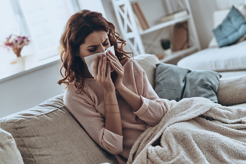 Top view of sick young women blowing her nose using facial tissues while sitting on the sofa at home, How to Allergy-Proof Your Home for Spring | Indoor Air Quality in Savannah