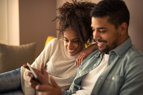 African american couple watching favorite TV show on a tablet, How AC and Heating Maintenance Saves You Money | Old Coast HVAC