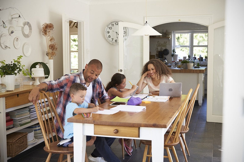 Parents Helping Children With Homework At Table, Duct Testing and Sealing Improves Your Comfort and Saves Money | HVAC