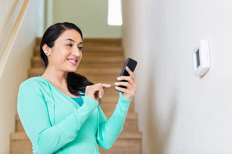 Hispanic woman adjusts thermostat with smart phone, 3 Features You Want in Your Smart Thermostat | HVAC, in Savannah, GA