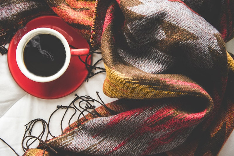Cozy winter home background, cup of hot coffee with marshmallow, warm knitted sweater on white bed background, vintage tone, Why You Should Get Solar Panels This Winter | Solar, Install, in Savannah