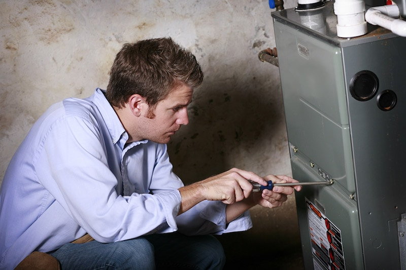 HVAC Technician Working on Furnace, How We're Different and More Responsive to Your Needs | Old Coast