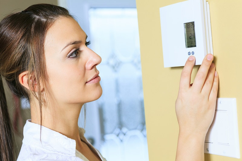 Young woman with brown hair setting a programmable thermostat, 3 Autumn Energy Tips | HVAC, Furnace, Heat Pump, in Savannah, GA